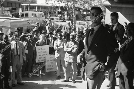 Led by the reverend Leslie Stradling, leaders of Methodist and Congregational churches held a protest rally in the Johannesburg Town Hall, to protest against South Africa's ninety-day law which enables police to detain and question suspects for up to 90 days without trial and be held in solitary confinement. Methodist churchman Ian Hughes seen addressing Africans outside the Town Hall ? they are not allowed inside under apartheid laws ? note woman with anti-South African placard who paraded up and down the street outside meeting