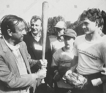 St. Louis Cardinals Hall of Famer Stan ?The Man? Musial (left) gives some batting tips to members of the AZS Warsaw baseball team before their game on in an international tournament at a soccer stadium in Kutno, Poland. Musial and former major league pitcher Moe Drabowsky, right of Musial. Both Polish-Americans, are on a week-long visit to help Poland?s fledgling baseball program
