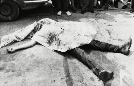 The body of NBC cameraman Neil Davis covered by newspapers after he was killed in cross fire between coup leaders and pro government soldiers in front of a military radio station in Bangkok, Thailand on