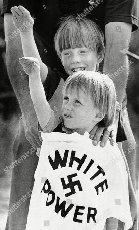 "Two boys raise their arms as an adult holds a ""White power"" T-shirt in front of them during a rally near Benson, N.C. Dozens of Nazis, Ku Klux Klansmen and right-wing sympathizers attended the rally. Historian David Cunningham says the KKK dwindled to nearly nothing during the 1970s and '80s"
