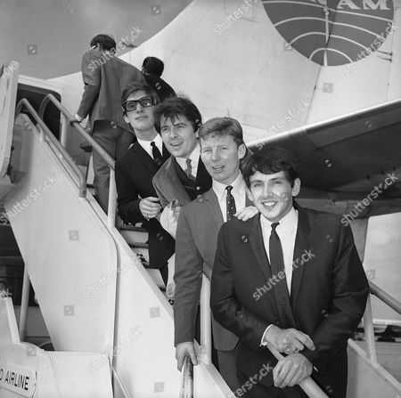 Pop band, the Searchers are, from left: Chris Curtis, Mike Pender, John McNally, and Frank Allen, shown leaving London Airport, for their third tour of the United States. The group later goes to New Zealand and Australia