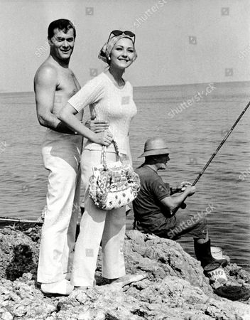 """American actor Tony Curtis takes the sun with his wife, German actress Christine Kaufmann on the rocks near Nice, south of France, during a break from filming """"You're Dead Right."""" Despite all the attraction, a local fisherman carries on regardless"""