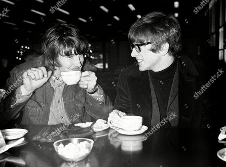 British pop singers Peter Asher and Gordon Waller, at left, of Peter and Gordon, sit drinking coffee at London airport before leaving for a tour of South Africa on