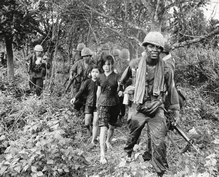Stock Image of U.S. paratroopers of the 1st Battalion, 173rd Airborne Brigade lead two girls from a captured Viet Cong training camp in the Long Nguyen area, . The girls, 17 and 14, said they had been at the camp for two and three months respectively. The paratroopers destroyed the camp