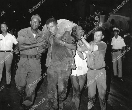 Pfc. Charles Boyer, 25, of Philadelphia, shows signs of exhaustion as he carries the body of a terrorist victim after in explosion, in Saigon. Boyer dug through debris with his bare hands until he collapsed from the strain. The army truck driver was taken to hospital but rushed back to continue rescue work as soon as he recovered. The explosion, in a government information office, killed eight and wounded 10 to 15 persons