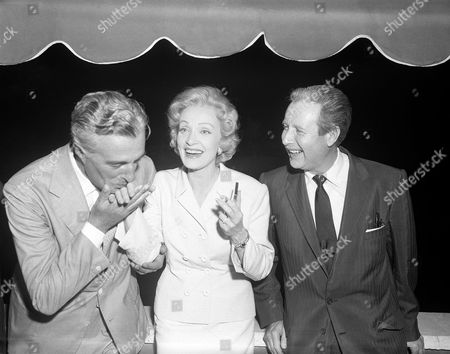 """Marlene Dietrich, Vittorie De Sica, Arthur O'Connell The Italian film company """"Titanus"""" gave a cocktain party in honor of the cast of """"The Monte Carlo Story"""" who have arrived from Monte Carlo to finish the picture in the """"Titanus"""" studios. Among the stars present were Marlene Dietrich, Italian producer-director-actor Vittorio De Sica; Arthur O'Connell, who plays one of the leading parts in the film; young U.S. Actress Natalie Trundy, who has the juvenile lead in the picture, and the director Sam Taylor. Vittorie De Sica kisses Marlene Dietrich's hand, while Arthur O'Connell is looking smilingly at them in Rome, Italy"""