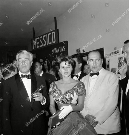 """Vittorio de Sica, Roberto Rossellini, Giovanna Ralli At the entrance of a Venice Lido cinema in Venice, Italy, Italian actor-director Vittorio De Sica, left, Italian actress Giovanna Ralli, center, and Italian director Roberto Rossellini, right, arrive for the showing of the film """"Il Generale della Rovere"""" (General della Rovere) which is presented for the current Film Festival in Venice. The movie, directed by Rossellini and starring De Sica and Giovanna Galli, scored one of the greatest successes of the Festival. This was Rossellini's first major work in Italy after several years"""