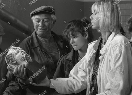 """German actress Judy Winter (Beate Richard), right, holds an Egyptian sculpture at the set with Katja Woywood, and Horst Niedorf, as they shoot a scene for the movie """"Der Schatz im Niemandsland"""", in West Berlin, West Germany, July 1986"""