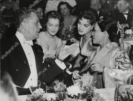 """Actor chats Viktor de Kowa chats with Actresses Romy Schneider, Margit Saad and his wife Michi Tanaka, from left to right, at the film ball in the Hotel Esplanade in West Berlin, Germany during the International Film Festival """"Berlinale&quot"""