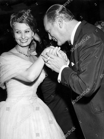 """Stock Picture of Loren, Sophia /1 West German actor Curd Juergens, right, holds the hands of Italian actress Sofia Loren (maiden name Sofia Scicolone) with a cigarette tucked between the fingers of his left hand, during the filmball of the International Film Festival """"Berlinale"""" in West Berlin, West Germany"""