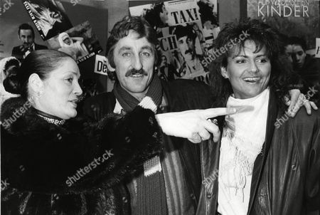 """Domenica Niehoff, Europe's most famous former prostitute, points with her finger past movie director, actor, Frank Ripploh, with Gaby Sievers, right, former body building world champion, as they stand in front of a poster of their movie """"Taxi to Cairo"""", after the premier at the """"Broadway"""" cinema in Hamburg, West Germany, . Both Niehoff and Sievers have play lead roles in the movie"""