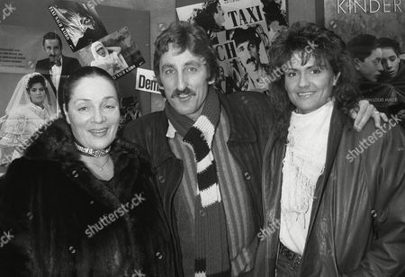 """Domenica Niehoff, Europe's most famous former prostitute, left, poses with movie director, actor, Frank Ripploh, and Gaby Sievers, right, former body building world champion, as they stand in front of a poster of their movie """"Taxi to Cairo"""", after the premier at the """"Broadway"""" cinema in Hamburg, West Germany, . Both Niehoff and Sievers play lead roles in the movie"""