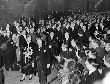 Winston Churchill Sir Winston Churchill, 80, leaves Westminster Hall in London, after receiving from the members of Both Houses of parliament an illuminated address and a portrait of himself by Graham Sutherland. Next to Churchill is Lady Churchill, and behind them follow Clement Attlee, leader of the opposition, and Mrs. Attlee. Behind Attlee, at right wearing glasses, is Lord Salisbury