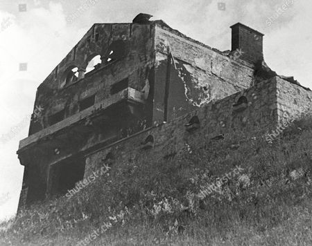 """Hitler's famous """"Berghof"""" (mountain house) is only a bomb-ripped, fire-scarred shell near Berchtesgaden, Germany on . British and American bomber planes hit it in a raid on April 25, 1945, just two weeks before the war ended. Then German SS troops set it afire with explosives just before the French troops captured the place on May 4. Souvenir hunters completed the destruction. They carried away even the marble steps, the oak paneling from the walls, and the tile from Hitler's and Eva Braun's bathrooms"""