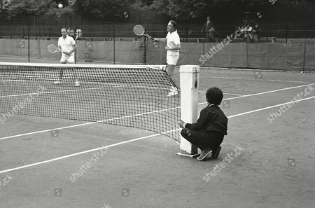 Young Timothy Shriver watches in foreground as his father, U.S. Ambassador to France Sargent Shriver, plays in the veterans tournament at Roland-Garros stadium in Paris on
