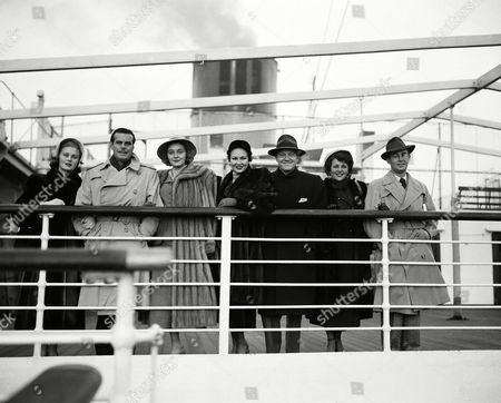 On the rail of the ocean liner Mauretania at Southampton, England on are: Joan Caulfield, Billy DeWolfe; Patricia Neal; Virginia Mayo; her husband, Michael O'Shea; Mrs. Alan Ladd, Sue Carol, and Alan Ladd. They have come for the Royal Command film performance, shortly to take place in London
