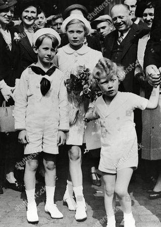 """Prince Baudoin, left, Princess Josephine Charlotte, center, and Prince Albert, right, children of King Leopold of Belgium, at Antwerp before boarding the """"Belgia"""" to go to Sweden for a holiday with their relatives, on"""