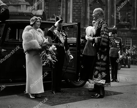 Stock Photo of Britain's King George VI and Queen Elizabeth paid a lightning visit to Belfast. They arrived in the Royal yacht, Victoria and Albert, proceeded up the river Lagan, and drove through cheering crowds to the city hall, and attended a garden party. The King and Queen being received by the Mayor of Belfast, Sir Crawford McCullagh, at the city hall in Belfast, Northern Ireland, on