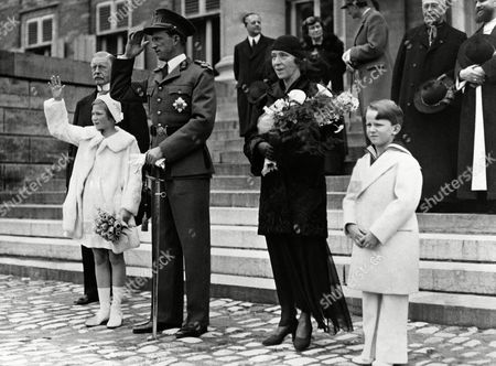 Numerous special trains were run into Brussels on carrying people from the Belgian province of Limbourg, who came to pay homage to King Leopold and the Royal family. The marched in procession past the King outside the Royal palace in Brussels. From left to right are: Princess Josephine Charlotte, King Leopold of the Belgians, Queen-mother Elizabeth and little Prince Baudouin seen during the march past of the people of Limbourg on May 9, 1937 in Brussels, Belgium