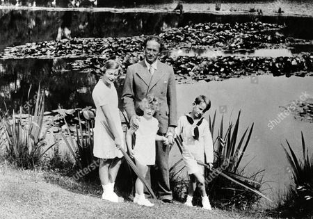King Leopold III of Belgium and his children. They were taken at the Royal Palace at Laeken, in the grounds which are such a playground for the family. Princess Josephine Charlotte, left, is now eleven years old, Prince Baudouin, right, the heir apparent, eight, and Prince Albert four. The King and his children by the side of one of the ornamental pools in the grounds of the Royal Palace at Laeken, Brussels on