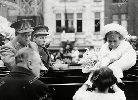 King Leopold III of the Belgians opened the Ghent Flower show at which a number of British horticulturists are exhibiting. King Leopold III, left,and his brother, Prince Charles watch Princess Josephine Charlotte reviewing a bouquet from a young patriot at the palace of flowers during their tour, on