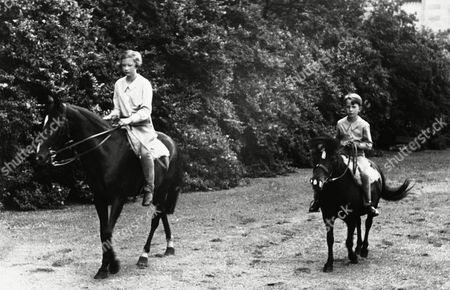 The children of King Leopold of the Belgians, playing in the grounds of the Royal Chateau of Laeken, Belgium, on . Princess Josephine Charlotte and Prince Baudouin are seen on horseback