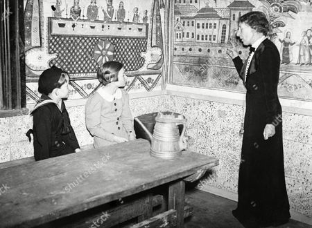 Young Prince Baudouin and Princess Josephine Charlotte, children of King Leopold of the Belgians, in a reconstructed house at the Swedish folklore exhibition, in Brussels, Belgium, on