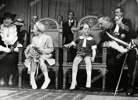 Prince Baudouin and Princess Josephine Charlotte of Belgium watched the celebrated procession of the Holy Blood through Bruges,, features of which are explained to them by members of the court seated on either side of their Thrones