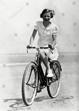 Princess Josephine Charlotte, 11 years old daughter of King Leopold of the Belgians, is now on holiday here at La Panne. She is staying in the royal palace occupied by the Belgian Royal family here during the war. Princess Josephine Charlotte riding her bicycle along the front at La Panne, Belgium, on