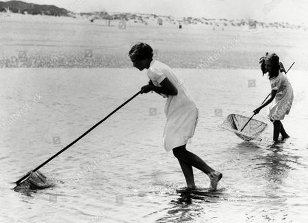 Princess Josephine Charlotte, 11 years old daughter of King Leopold of the Belgians, is now on holiday here at La Panne. She is staying in the royal palace occupied by the Belgian Royal family here during the war. Princess Josephine Charlotte, nearest, enjoying a shrimping expedition at La Panne, Belgium, on