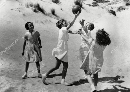 Princess Josephine Charlotte, 11 years old daughter of King Leopold of the Belgians, is now on holiday here at La Panne. She is staying in the royal palace occupied by the Belgian Royal family here during the war. Princess Josephine Charlotte, white dress, enjoying a ball game with friends on the sand dunes at La Panne, Belgium, on