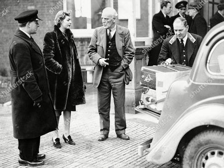 Stock Photo of David Freeman-Mitford, Lord Redesdale and his daughter Deborah Mitford talk as the luggage is loaded to a car in Folkstone, England on . Deborah Mitford then travelled to High Wycombe with her sister Unity's luggage