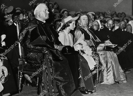 Young women catholic students of Belgium celebrated the jubilee of their movement with a special assembly at the Heysel Palace, Brussels. Princess Josephine Charlotte sitting between Cardinal Van Roye, Archbishop of Marlines, left, and Monseigneur Micara, the Papal Nuncio, at the jubilee assemble at the Heysel Palace, Brussels, on