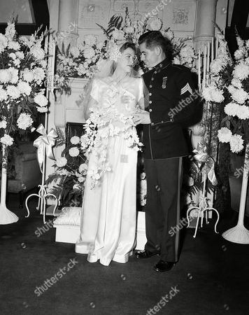 Actress Eleanor Powell and Sgt. Glenn Ford of the U. S. Marine Corps, former Hollywood actor, after their marriage, at the Beverly Hill, Calif., home of the bride. After a ten day honeymoon Miss Powell returns to her film work and Ford reports to camp Pendleton where he is attached to the Marine Corps photographic section