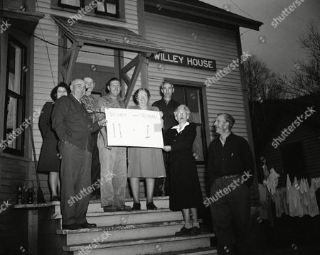Stock Picture of Voters of the tiny mountain hamlet of Hart's Location, N.H., show how they voted for Governor Thomas E. Dewey 11-1 as they stand outside the voting place on . Left to right; Mrs. Macomber, town clerk Douglas Macomber; Joseph Burke, Preston King, Mrs. George Morey and George Morey. The town, first in the country to report complete returns, voted at dawn
