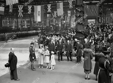 Britain's King George VI and Queen Elizabeth left London for Portsmouth where they will board the liner Empress of Australia for the trip to the United States and Canada. They drove with many members of the Royal family and a captain's escort of the famous Life Guards to London's Waterloo Station, where they boarded the Royal train. Members of the Royal family and members of the cabinet were waiting to bid them bon voyage. King George saying goodbye to Lord Halifax at Waterloo Station on May, 6, 1939. Members of the cabinet look on. From left to right are Lord Crewe, Prime Minister Neville Chamberlain, Sir Samuel Hoare, Lord Halifax and Sir Thomas Inskip. Queen Elizabeth, with Princess Elizabeth and Princess Margaret are talkting with an officer on the left