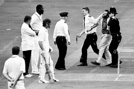 MCC v Transvaal cricket match, Lords - An Anti-Apartheid protester is escorted off the pitch after seven men stormed the square in an attempt at disruption, after the first ball was bowled by the West Indian Joel Garner (next to the umpire). This was the first visit to Lords by a senior South African side for 27 years.