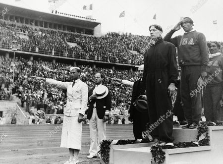 Jesse Owens, Ralph Metcalf, Tinus Osendarp The ceremony honoring the three winners in the 100 meter Olympic final in Berlin, which was won by Jessie Owens, U.S.A, middle, second was Tinus Osendarp, Holland, front, and third Ralph Metcalf, U.S.A. (extreme right