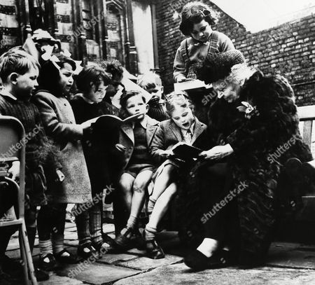 """Maria Montessori, Italian educator, with a large group of children from one of her """"works"""" in Italy"""