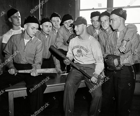 "Ecruits at the Bainbrige Naval Training center Stan Musial in baseball cap, tells other recruits at the Bainbrige Naval Training center in Bainbrige, Md., how he used to slug'em for the St. Louis Cardinals. Musial reported today for ""Boot"" training after his induction into the Navy at Pittsburgh. In the background (left to right) Bruce Hollway of Miami, Fla, Delmas Kimmons of Miami Fla, J.P. Bodie, Newberry S.C. Jack Coyne, of Miami Fla, Robert Craft of St. Louis Mo, Bill Sorensen, of Thomasville, Ga, Ben Chalmers of Phili. Pa, R.L. Beckham of Miami Fla"