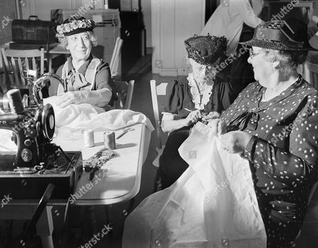From left to right are Miss Adah C. Sherman using sewing machine, ; Miss Julie M. Lippman, knitting and Mrs. Helen Wainwright sewing a sweater who are a trio of names well-known in the past of the theater