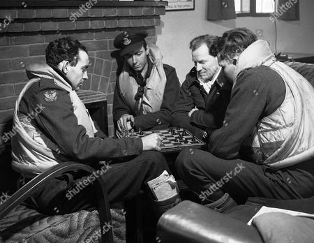 Members of an American Eagle Squadron, now flying with the Royal Air Force, are seen deeply interested in a game of chess, at their airfield somewhere in England, while waiting for their next call to scramble. Left to right; Pilot Officer Ben F. Mays, J.M. Kelly, Pilot Officer H.H. Strickland, and Pilot Officer Tom Andrews