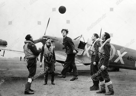 Members of the Royal Air Force Eagle Squadron relax with some heading practice, while awaiting the call for action at their base, . From left to right are Pilot officer Ben F. Mays, Wharton, Texas; Pilot officer Tom Andrews, Costa Mesa, Calif.; a member of the ground staff; W. T. O'regan, of Los Angeles; J. M. Kelly, Oakland, Calif