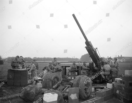 Virginia soldiers form a human chain to feed their anti-aircraft gun a shell in readiness for any enemy air attack. The gunners protect an airdrome, somewhere in England, on . From left to right are: Pfc. Robert W. Dodson, Danville Pfc. Frank B. Clay, Danville; Corporal James O. Long, Vinto, Private Charles W. Wright, Alvarado; Pfc. Conley S. Goodpasture, Roanoke, Pfc. William Hoover, RFD, Danville; Pfc. Robert E. Griffith, RFD Alexandria; Private Carl A. Martin, Fieldale; Pfc. Robert K. Ellis, Moneta; Pfc. Elder L. Harris, Danville; Corporal Morris O. Walter, Roanoke; Pfc. Jessie T. Epperso, Hurts; Pvt. Ivis Chaney, Bass Pfc. James R. Draper, Roanoke