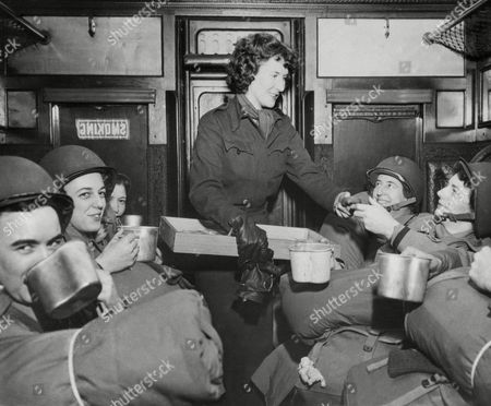 U.S. Army nurses have a snack of doughnuts and coffee on a troop train en route to their post in England after debarking from a transport, . Doughnuts are furnished by an American Red Cross worker. Left to right: Lieutenant Agnes R. Glode, Littleton, N.H.; Lieutenant Ruth E. Fairweather, Pawtucket, R.I.; Lieutenant Vera E. Esty, Marlboro, Mass.; Red Cross worker H. Broughton, Newark, Ohio; Lieutenant Vera B. Griffin, Beberidge, Mass.; and Lieutenant Theresa J. Grady, Hastings-on-Hudson, New York