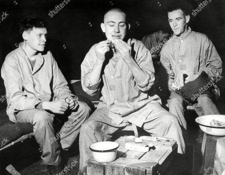 """Pfc. Thaddeus Michalik, Michigan City, Ind., center, gives himself a shave after he was freed from a German prison camp on . He is using a """"release kit"""" given to him by the American Red Cross. At left is Pfc. John Niven, Venice, Calif., and right, Pvt. Dennis Murray, Gillespie, Ill. Location unknown"""
