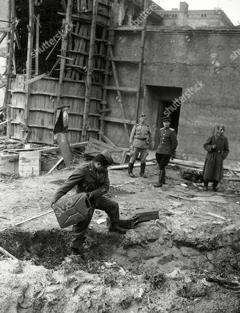 Stock Image of Pfc. Harvey Natchees of Myton, Utah, inspects the site outside entrance to underground shelter in the Reichschancellery building in Berlin, Germany, where a German Chancellery guard reported he saw the bodies of Adolf Hitler and Eva Braun burning