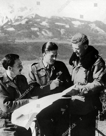 Lt. Carl Bieders, right, of San Antonio, Texas, chats with relatives of the king and queen of England who were released from a prison camp in the Tyrollean Alps by the American Seventh Army in Germany on . The Britians are Captain Master of Elphinestone, nephew of the queen, left, and Lord George Henry Lascelles, center, nephew of the king