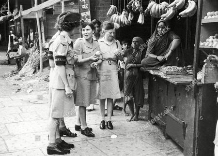 These airwomen buying fruit at an Indian market, are given advice by members of the W.A.A.F. Police. They are left to right: Corporal Marion Jacklin, of 129 Haslingden Old Road, Rawtenstall, Rossendale, Lance; Sergeant Annie Miller of 8 Westmorland Street, Glasgow; Corporal Jessie Brown of I, Cochrins Place, Rosewell, Midlothian; and Leading Aircraftwoman Pat Walton of 44 Wouldham Road, Borstal, Rochester, Kent