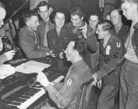 American soldiers attached to Lt. Gen. Joseph W. Stilwell's headquarters in New Delhi, India, gather around a piano to greet a newly arrival WAC sergeant with music. From left to right are leaning on piano, Pvt. Bob Jefferis, of Richmond, Ind.; Pvt. David Larson, of Chicago Ill.; WAC T/3 Alleen March, of Chicago; Pvt. Neville Winkler, of Providence, R.I.; and T/Sgt. Dick Harnden, of El Paso, Tex